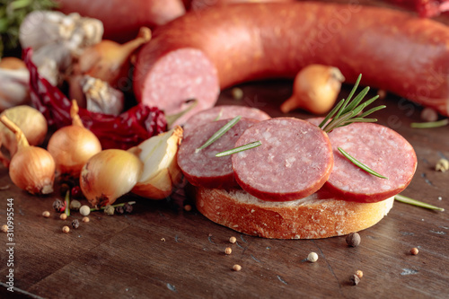 Sandwich with salami on a old wooden table. Wallpaper Mural