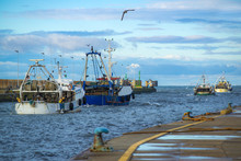 Chalutiers Quittant Le Port Sous Un Ciel Nuageux