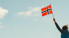 Hand Holds Norwegian Flag Against Sky