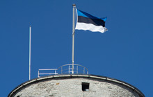 Estonian Flag On The Tower Against The Blue Sky On A Bright Sunny Day