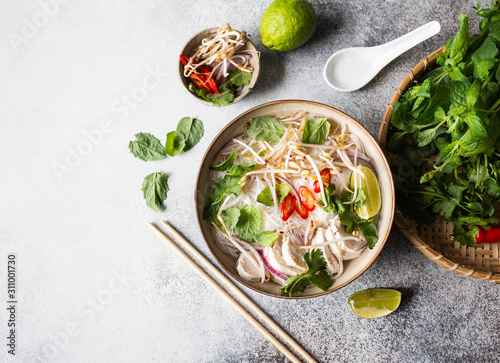 Leinwand Poster Traditional Vietnamese soup- pho ga in bowl with chicken and rice noodles, mint and cilantro, red onion, chili, bean sprouts and lime on grey background