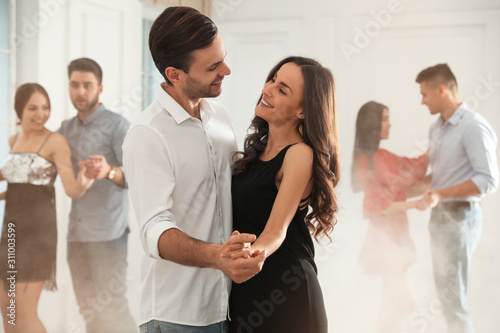 Lovely young couple dancing together at party Wallpaper Mural