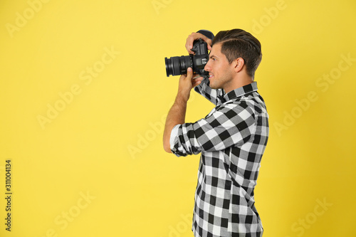 Obraz Professional photographer working on yellow background in studio. Space for text - fototapety do salonu