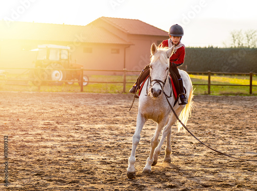 Leinwand Poster 8 year boy riding white horse during sunset at ranch