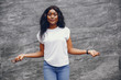 Cute black girl near gray wall. Lady in a white t-shirt and blue jeans.