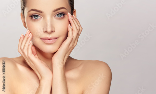 Obraz Beautiful young woman with clean fresh skin on face . Girl facial  treatment   . Cosmetology , beauty  and spa . - fototapety do salonu