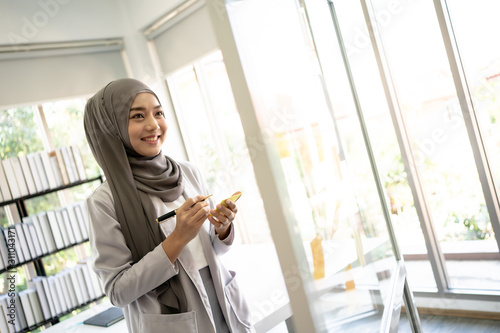 Fotomural Muslim Business Woman in Hijab with Documents at Workplace in Office