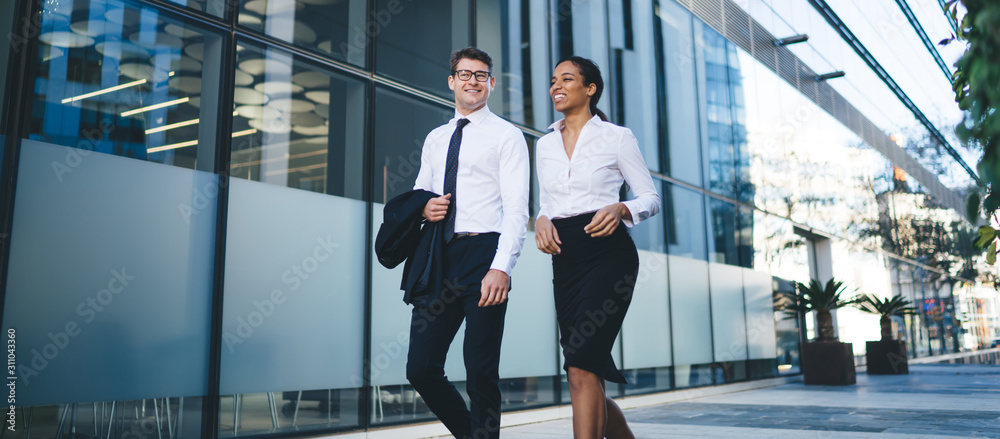Fototapeta Relaxed young coworkers walking on street Low angle of happy young diverse woman and man in elegant outfits walking and chatting cheerfully on background of city building