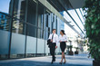 Contemporary smiling coworkers on street Modern elegant multiethnic woman and man strolling down street and chatting happily relaxing after work on background of glass building