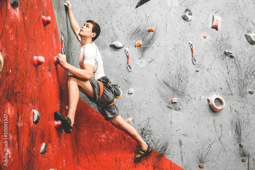 Fototapeta Sportsman climber moving up on steep rock, climbing on artificial wall indoors. Extreme sports and bouldering concept obraz