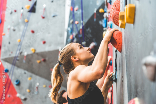 couple of athletes climber moving up on steep rock, climbing on artificial wall indoors Canvas Print