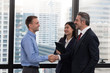 Senior executive shaking hands with young employee with secretary holding clip board in the office with building background