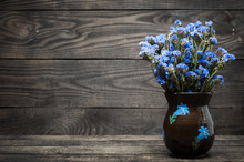 A Vase With Blue Flowers Stands On A Wooden Table. Wood Texture.