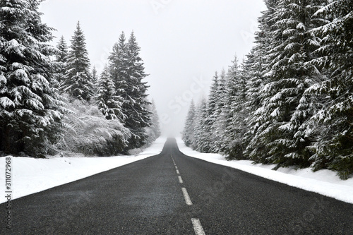 A dangerous slippery mountain road during the winter with low visibility Canvas Print