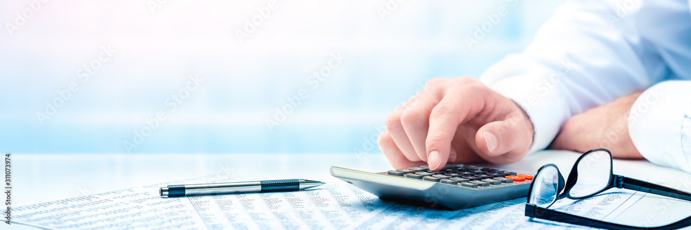 Fototapeta Business Man Using Calculator On Desk With Pen, Reading Glasses, And Financial Report- Business Accounting Concept