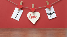 I Love You - Clothes Pegs With Wooden Hearts And Paper Notes Hang On Rope Isolated On Red Texture Background, With Space For Text