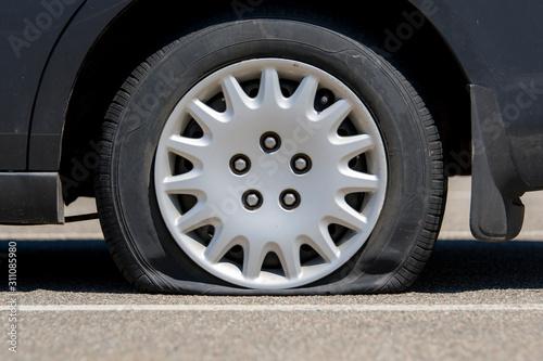 Flat tire on an unidentifiable black car Tapéta, Fotótapéta