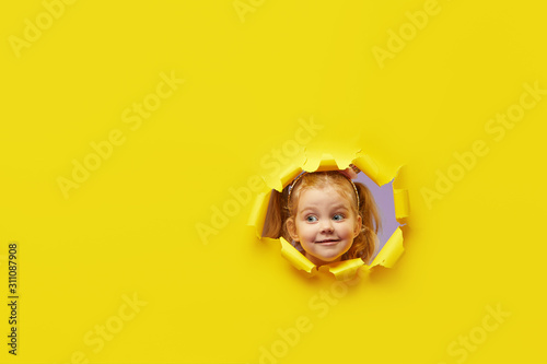 Fototapeta Little child looking, peeping through the bright yellow paper hole