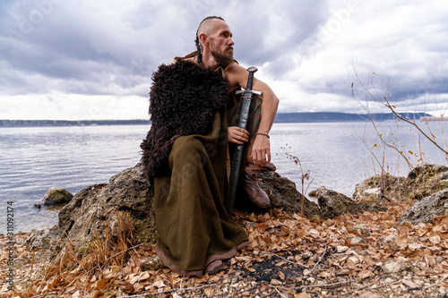 Viking sits on the river bank Canvas Print