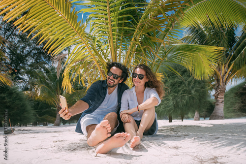 A pair of lovers take a selfie under a palm tree on a tropical beach