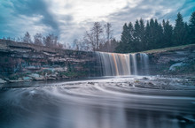 Long Exposure Photo Of Jägala Waterfall, 8 Meters High And More Than 50 Meters Wide Fall In The Lower Course Of The Jägala River. Estonia, Europe. Low Sun Casts Various Colors On The Water.