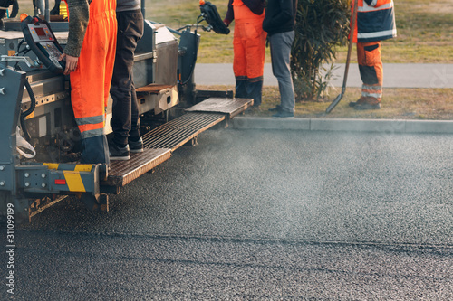 Asphalt paving. Paver machine and workers. New road construction.