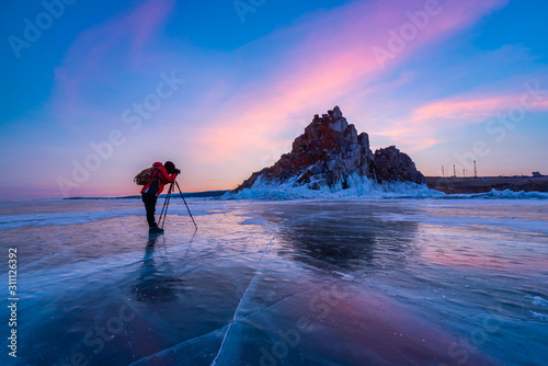 Photographer or Traveller using a professional DSLR camera take photo beautiful landscape of Baikal lake at sunset winter Canvas Print