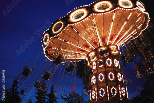 Carousel Merry-go-round in amusement park at a night city Canvas Print