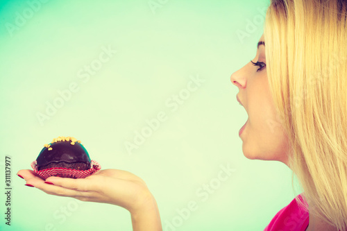 Photo Cute blonde woman about to eat cupcake