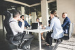 A team of young businessmen working and communicating together in an office. Corporate businessteam and manager in a meeting