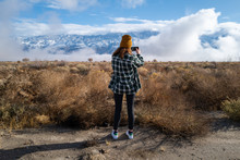 A Woman In A Vintage Flannel Shirt Takes A Photo With Her Phone Of Mountains And Clouds In Eastern California