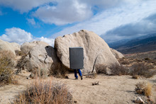 A Climber Carries A Crash Pad To A Boulder Problem In The Buttermilks Near Bishop, CA