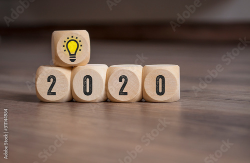 Cubes and dice with lightbulb and 2020 on wooden background