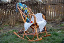 A Wicker Rocking Chair With Pl...