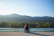 A Woman Sitting Alone By The Lake Looking At The Mountains With Green Nature Background