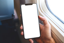 Mockup Image Of A Hand Holding A Black Mobile Phone With Blank Desktop Screen Next To An Airplane Window