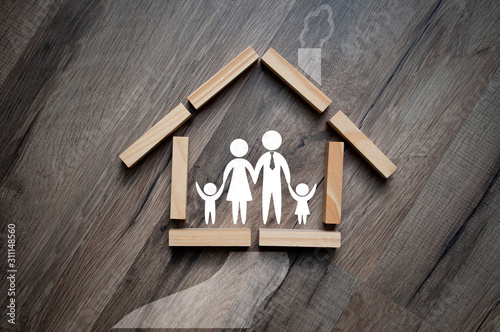 Fototapeta House made of wooden pieces with family stick figures on wooden background metaphor for dream of home ownership obraz