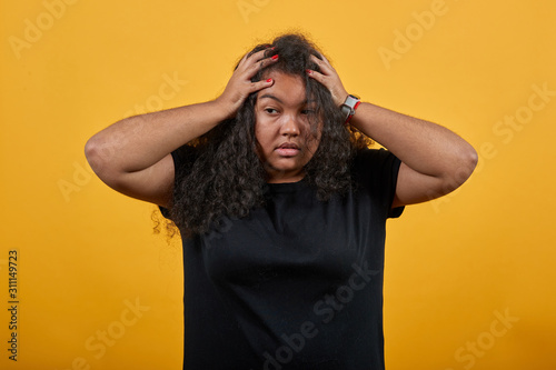 Cuadros en Lienzo Crazy afro-american young woman with overweight over isolated orange background wearing fashion black shirt keeping hands on head, corrects haircut