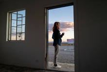 A Stylish Woman With Red Hair Smokes In A Doorway In The California Desert At Sunset