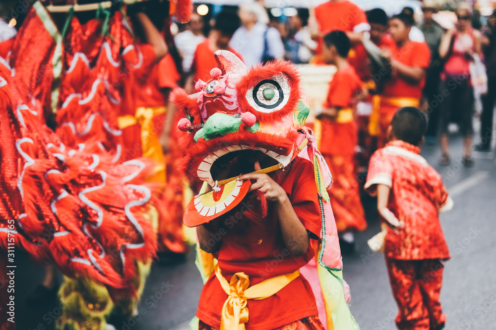 Fototapeta Lion dance during Chinese New Year celebration. Group of people perform a traditional lion dance.