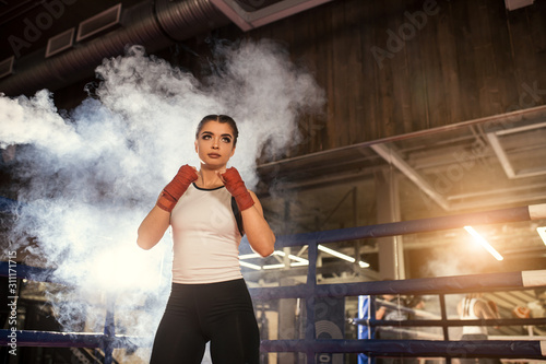 Valokuvatapetti young caucasian MMA girl in sports uniform ready to fight in boxing ring, red ba