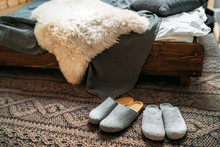 """The Two Pair Of Gray Home Slippers Near The Wooden Bed On The """"knitted Floor"""" In The Cozy Bedroom. Home Sweet Home Concept Image."""