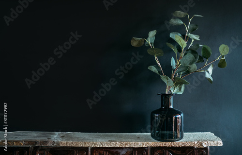 Green tree Branch putted into black glass vase on the natural stone mantel shelf on the black color wall background lit with side window light. Cozy home decor elements concept image.