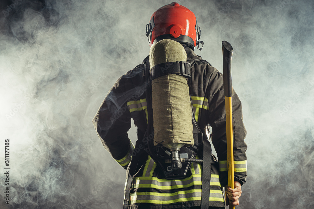 Fototapeta rear view on reverent, confident man working in fire station ready to save people from fire in emergency situations, wearing uniform and helmet