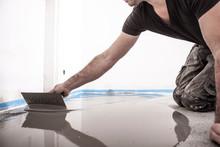 Bauarbeiter Rührt Ausgleichsmasse An, Spachtelt Den Fußboden Und Bereitet So Den Boden Für Das Parkettlegen Vor