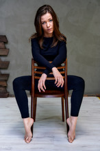 Vertical Photo On A Chair In A Stylish Interior In A Studio Of A Pretty Glamorous Brunette. Girl Sitting On A Chair In A Black T-shirt With Long Hair On A Color Fashionable Original Background.