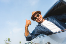 A Traveler Wearing A Hat Is Driving A Car And Then Pulling Himself Out Of The Car Window. And Thumbs Up This Picture Is About A Safe Journey By Car.