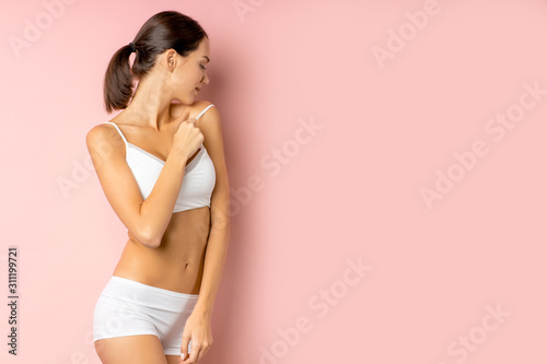 side view on attractive female brunette with tail hair, wearing white underwear. healthy life concept, isolated over pink background