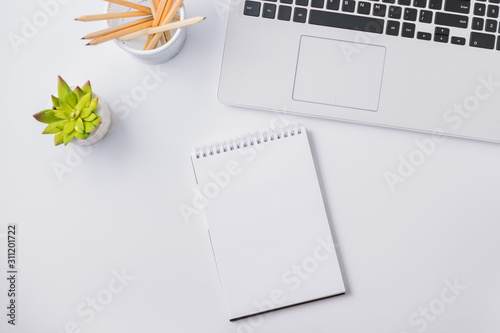 Obraz Flat lay composition with white laptop and mockup notepad on a white table - fototapety do salonu
