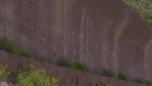 A Closeup Shot With An Upward Tilting View Of The Long Span Of A Fort?s Concrete Retaining Wall Built On Rocky Terrains.